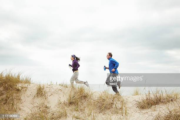 Couple exercising on sand dunes at beach