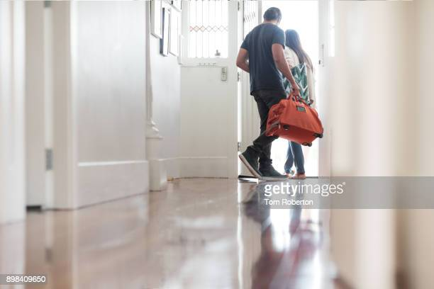 couple exiting house with luggage - leaving stockfoto's en -beelden
