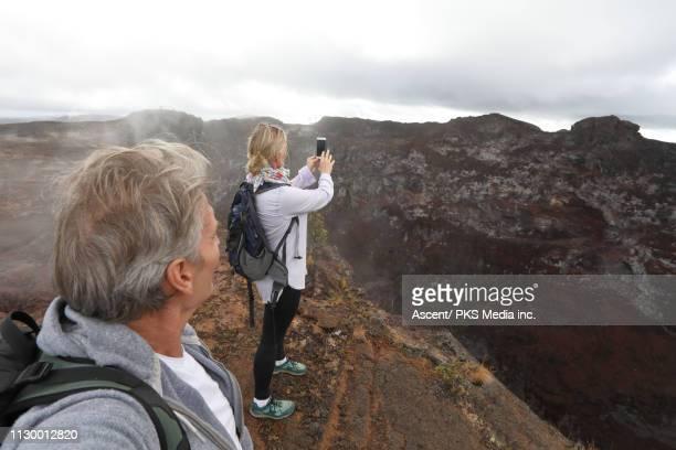 couple explores edge of crater in steam vents - ハワイ火山国立公園 ストックフォトと画像