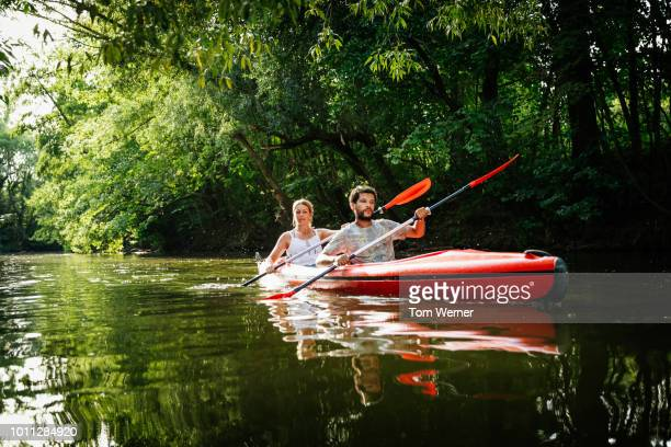 couple exploring canals in large kayak together - wassersport stock-fotos und bilder