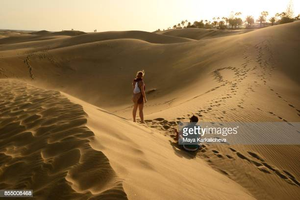 couple exploring maspalomas sand dunes, canary islands - canary islands stock photos and pictures