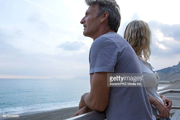 Couple face opposite directions above beach, sea