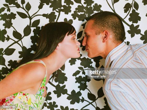Couple face to face in front of wallpaper