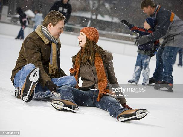 Couple falling while ice skating