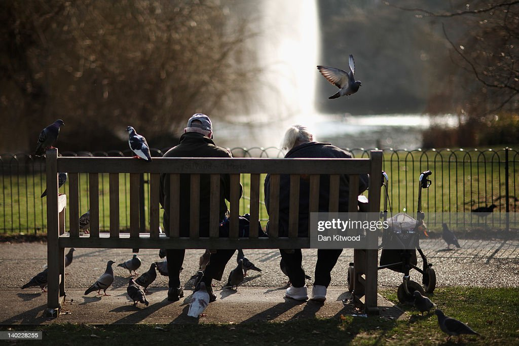 A couple feed pigeons in St James's Park on March 1, 2012 in London, England. After a recent cold snap Britain is expected to see a short period of unseasonably mild weather following one of the driest February's on record according to the Met Office.