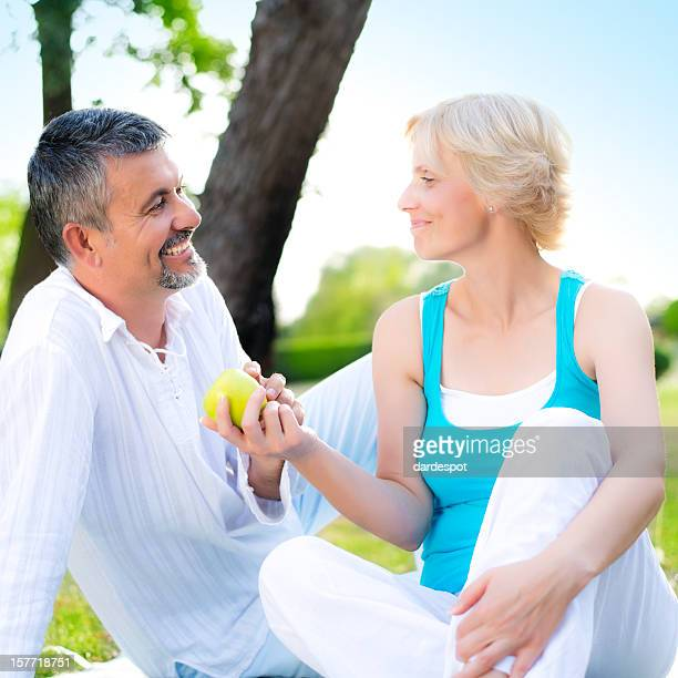 Couple feeding an green apple in nature