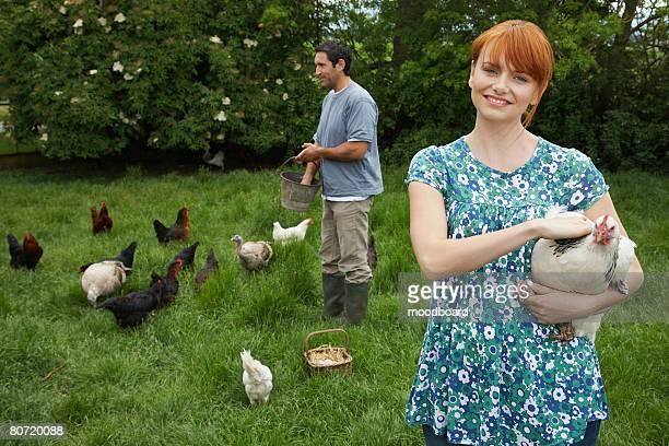Couple Feeding Chickens