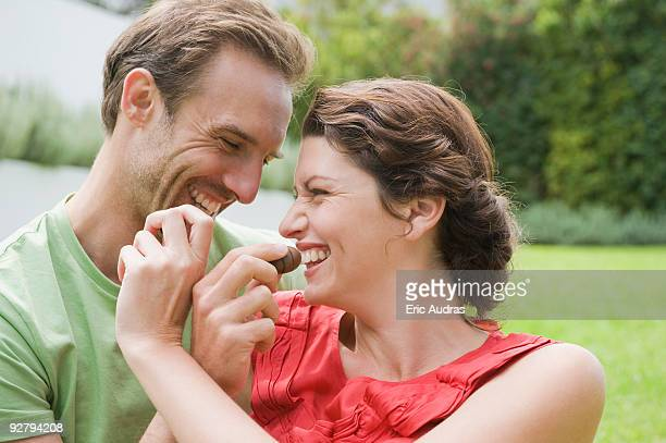 couple feeding chocolates to each other and smiling - couple chocolate stock pictures, royalty-free photos & images