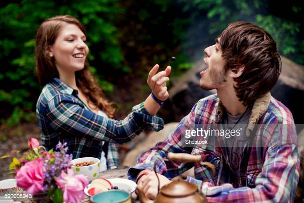 Couple feeding each other in forest