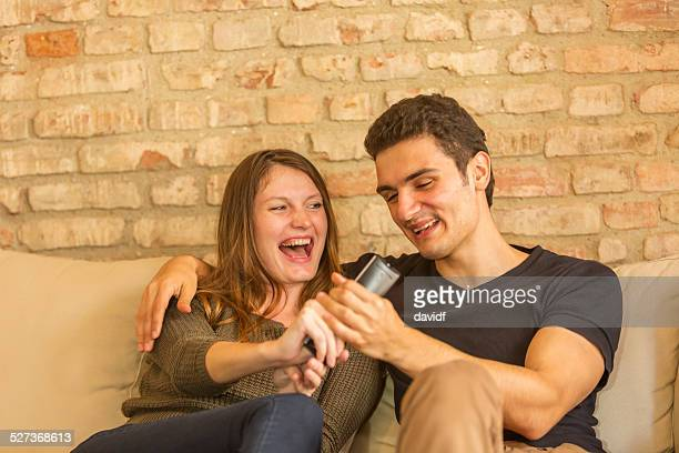 Paar kämpfen über die Fernbedienung für den Fernseher