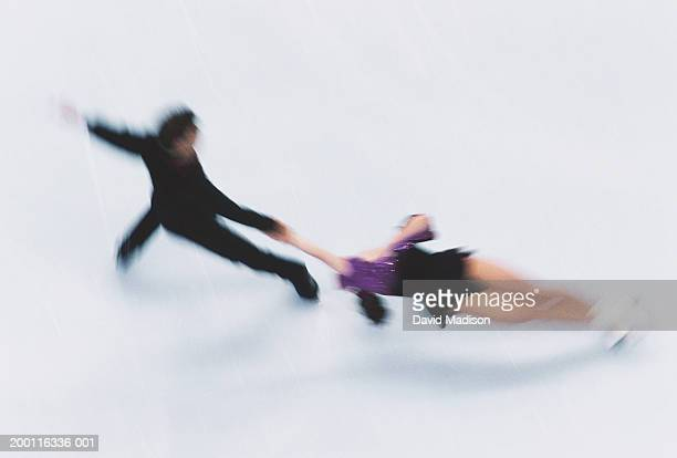 couple figure skating on ice, elevated view (blurred motion) - match sport stockfoto's en -beelden