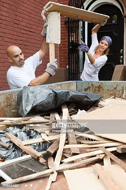 Couple filling skip with rubble