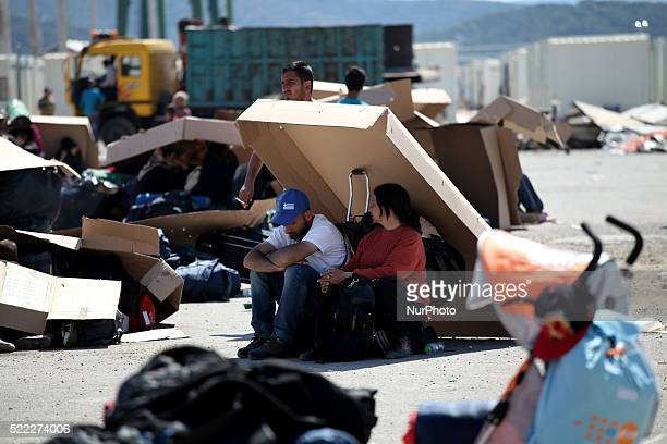 A couple finds shadow under cartons while waits to register Refugee camp in Skaramaga area a port town 11 km west of Athens A large camp is being...