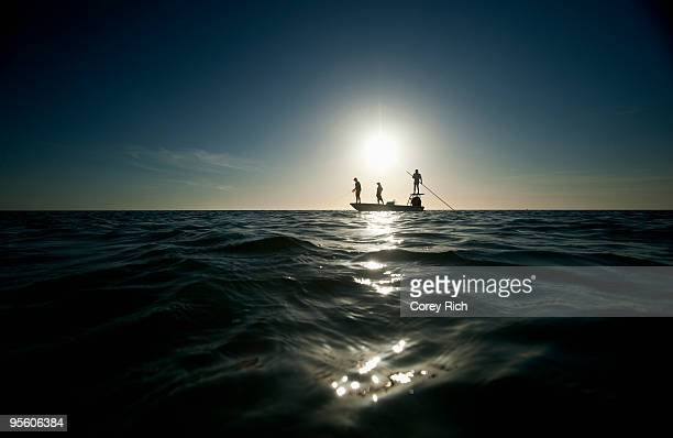 A couple fish as a man pilots a small boat in Florida. (silhouette)