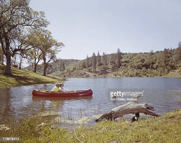 Couple fishing from canoe in lake