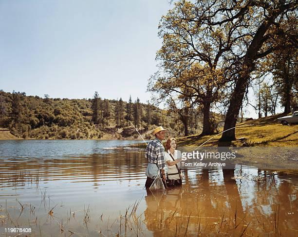 Couple fishing in lake, smiling