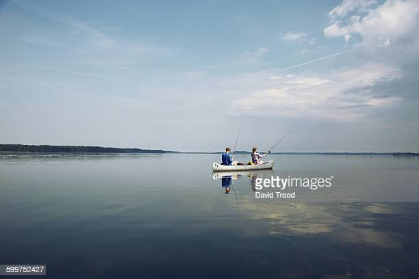 couple fishing on a quiet lake from a canoe. - bateau à rames photos et images de collection