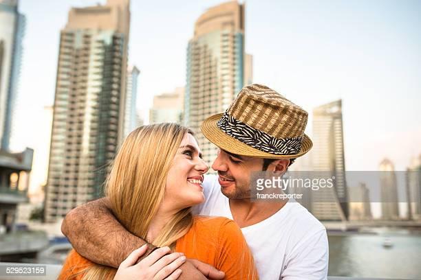 couple flirting against the skyline of dubai marina