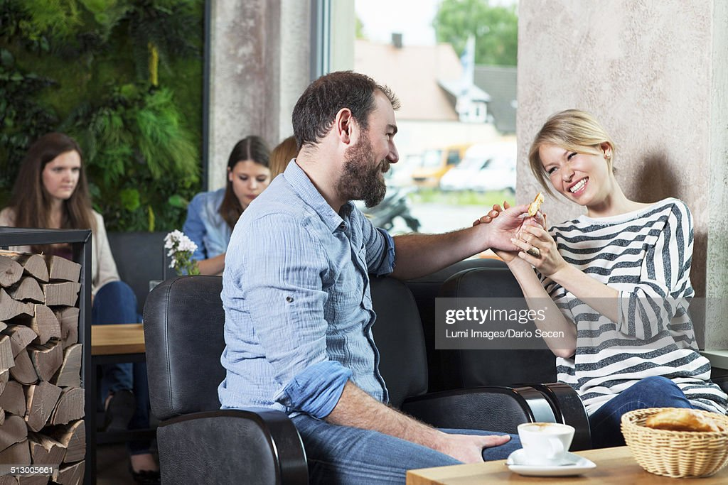Couple flirting in a cafe, people in background : Stock Photo