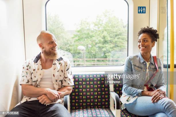 couple flirting on train - flirtare foto e immagini stock
