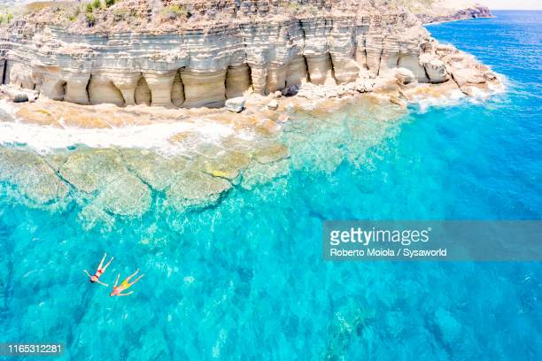 couple floating in sea, pillar of hercules, antigua - wonderlust stock pictures, royalty-free photos & images