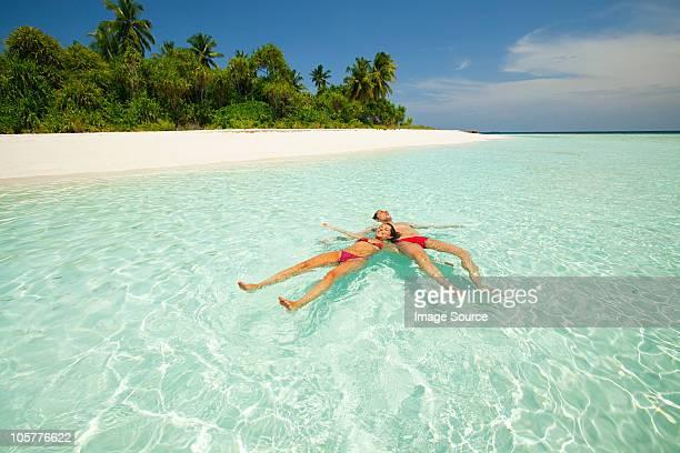 Couple floating in the sea, Baughagello Island, South Huvadhu Atoll, Maldives