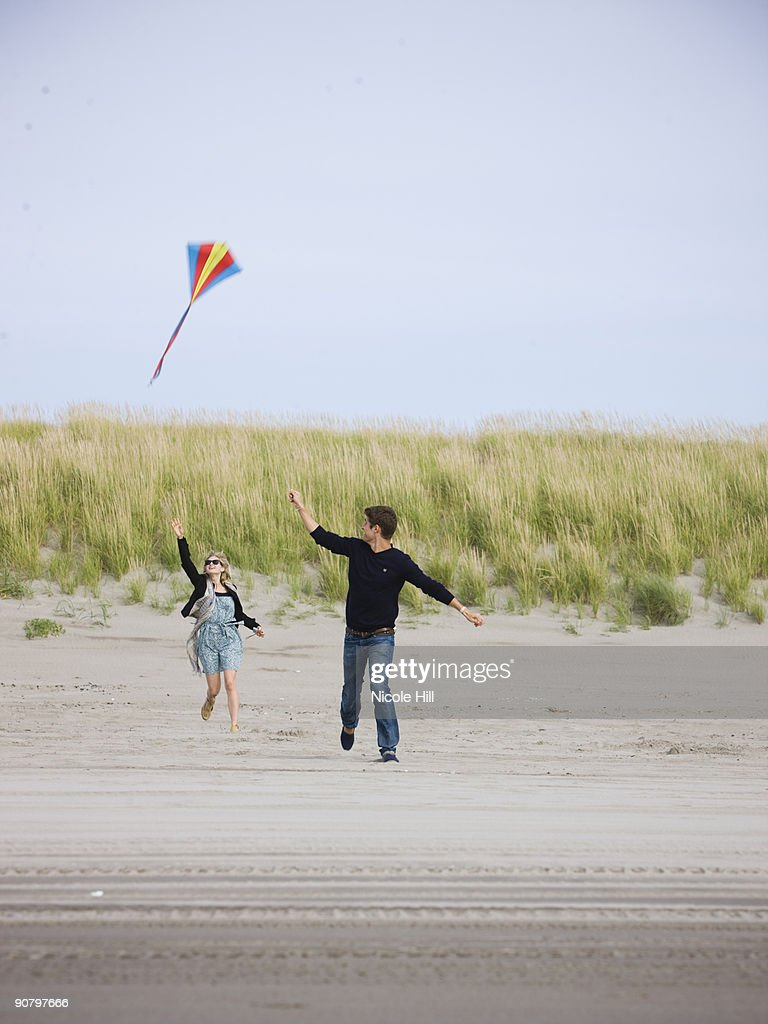 couple flying a kite at the beach : Stock Photo