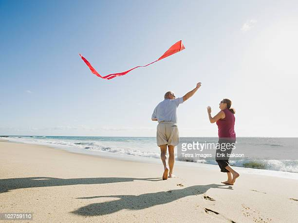couple flying kite on beach - kite toy stock photos and pictures