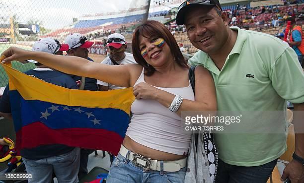 A couple follower of Venezuelan Tigres de Aragua show their national flag cheering for their team during the Caribbean Series game against Puerto...