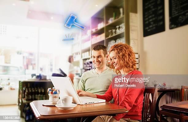 Couple following online auction on laptop