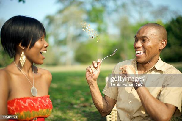 couple fooling around with breakfast cereal in a park. pietermaritzburg, kwazulu-natal province, south africa - pietermaritzburg stock pictures, royalty-free photos & images