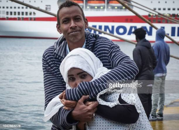 A couple from Togo pose for a photograph following disembark at the Port of Pireaus 29 September 2018 Thousand migrants and refugees are scheduled to...