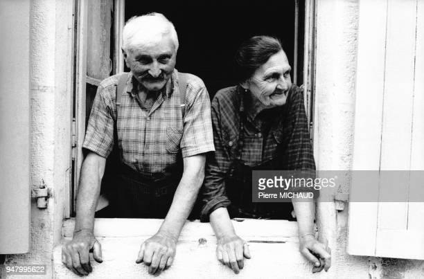Couple âgé à la fenêtre de sa maison en France en 1989