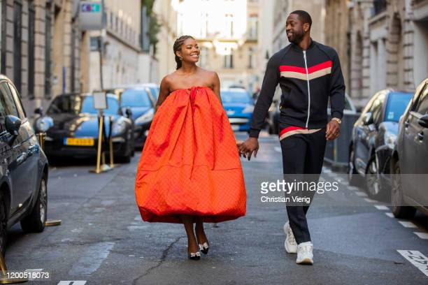 Couple Gabrielle Union is seen wearing orange off shoulder dress Christopher John Rogers and heels and Dwyane Wade wearing black track suit with red...