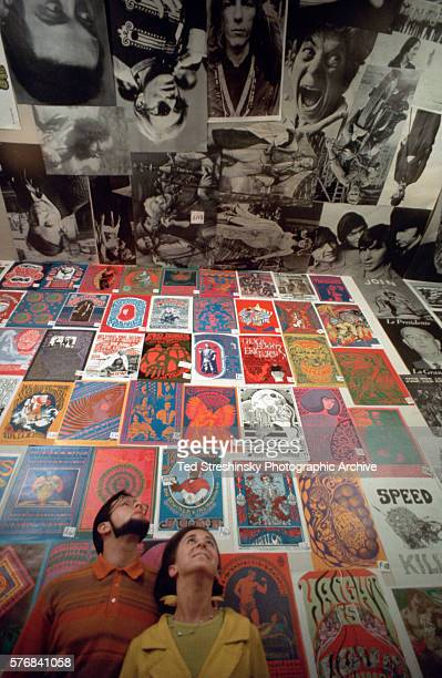 A couple gazes at the floor to ceiling posters in a popular psychedelic poster shop Print Mint in the Haight Ashbury district San Francisco 1967