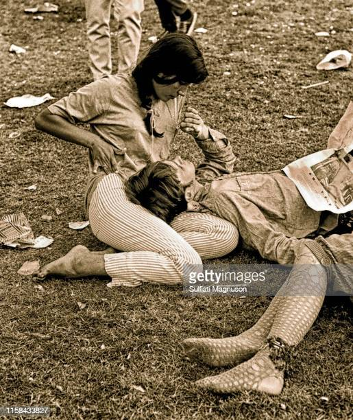Couple gazing, man focused on her shiny necklace, with fish-netted legs of entwined other couple at the 1st Elysian Park Love-In on March 26, 1967 in...