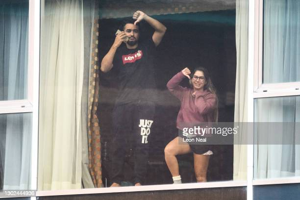 Couple gesture to the media from their room at the Radisson Blu, on February 16, 2021 in London, England. From yesterday, people arriving from 33...