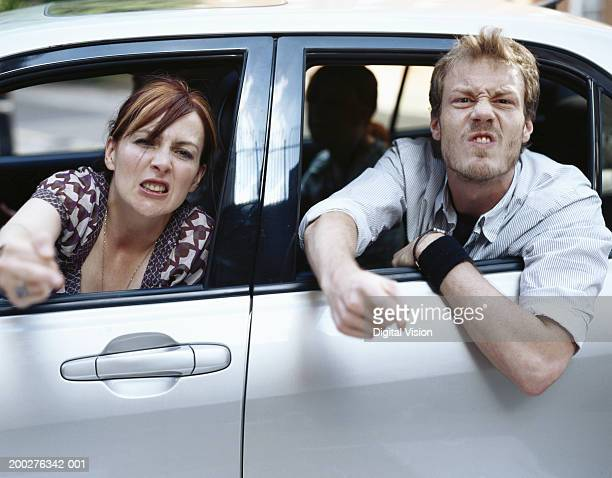 Couple gesturing aggressively out of car windows, portrait