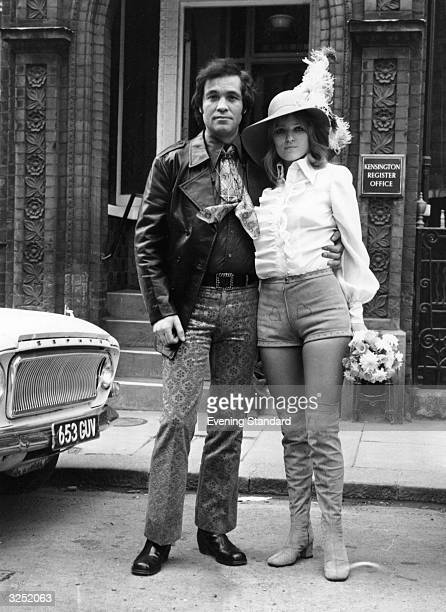 A couple get married at Kensington Registry Office she in the latest hot pants fashion and boots and he in paisley trousers