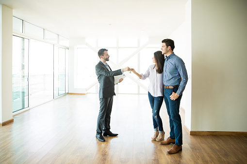 Couple Getting Keys From Realtor Of Their New Home 1023534670