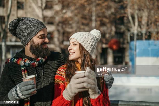 アイススケートの準備をするカップル - マフラー ストックフォトと画像