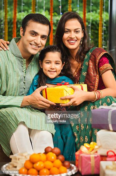 Couple giving gifts to their daughter on Diwali