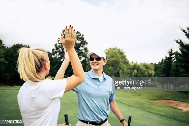 couple giving high five on golf course - trefferversuch stock-fotos und bilder
