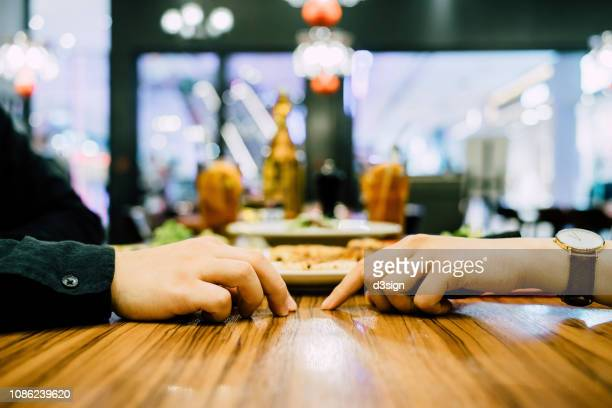 couple going on a first date and attempting to hold hands during a dinner date at a restaurant - cheating wife stock pictures, royalty-free photos & images
