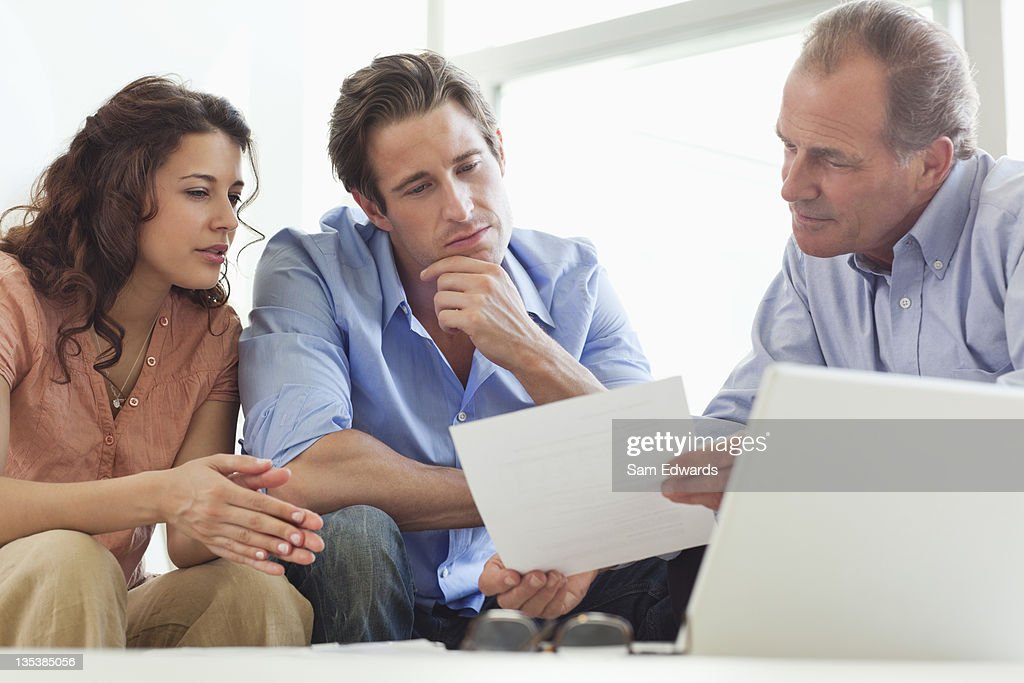 Couple going over paperwork with financial advisor : Stock Photo