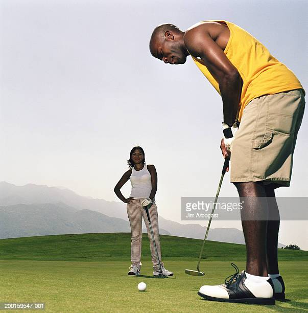 Couple golfing, woman watching while man prepares to putt