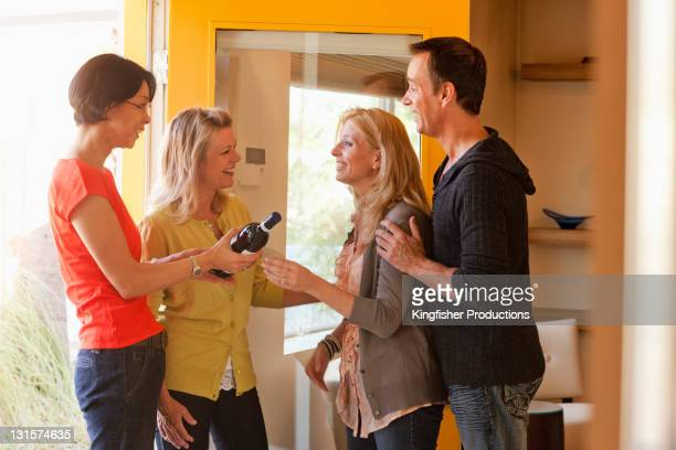 Couple greeting friends arriving with wine