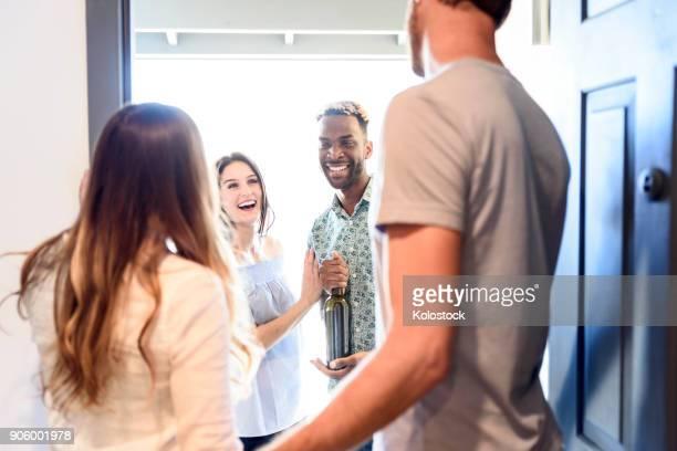 couple greeting friends bringing wine bottle at door - vriendje stockfoto's en -beelden