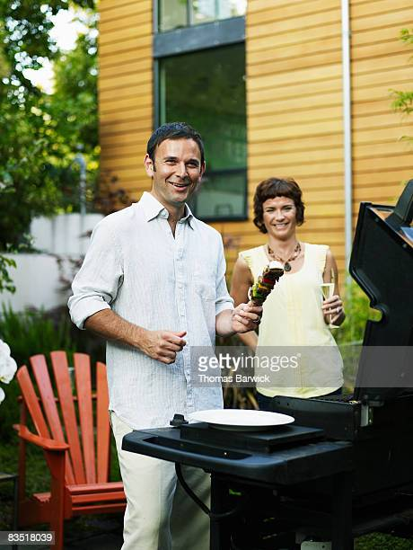 Couple grilling in backyard garden, laughing