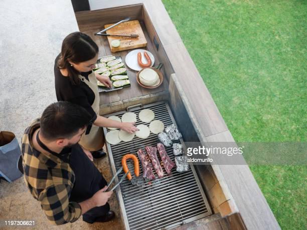 couple grilling together mexican food - carne assada imagens e fotografias de stock
